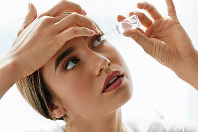 woman inserting eye drops